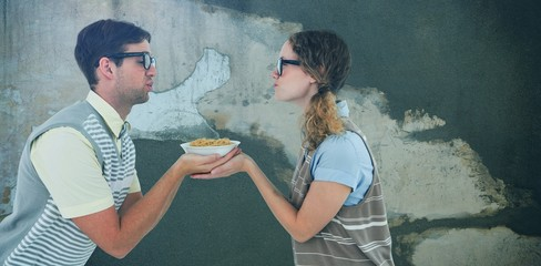 Composite image of geeky hipster couple holding pasta