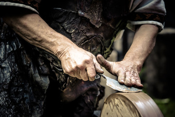 Mann beim Messer schärfen an der Schleifscheibe