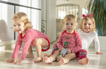 twins and elder sister sitting at home