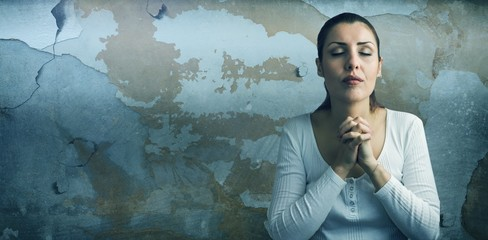 Composite image of beautiful woman praying with joining hands