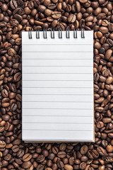 Background with spilled coffee beans and a notebook with white lined cards