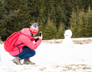 Girl taking a photo of a snowman with a smartphone