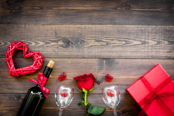 Celebrate Valentine's day. Wine, glasses, red rose, heart sign, goft box on dark wooden background top view copy space