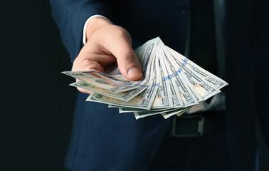Businessman holding bribe on black background