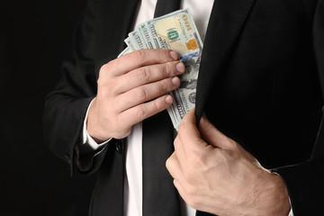 Businessman putting bribe in pocket on black background
