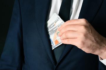 Businessman putting bribe in pocket, closeup
