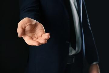 Businessman demanding bribe on black background