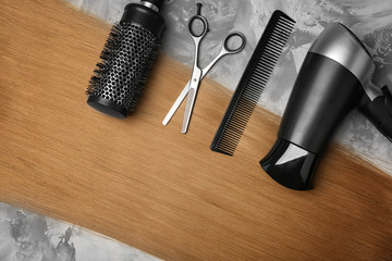 Professional hairdresser's set and blonde hair on grey background