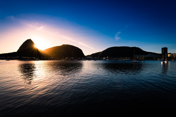Wall Mural - Silhouette of the Sugarloaf Mountain with Sun Rising Behind It, Rays of Light Visible