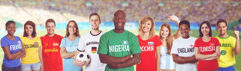 Nigerianischer Fussball Fan im Stadion mit Gruppe internationaler Fans