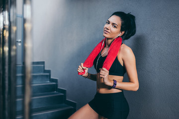 Horizontal portrait of sporty attractive brunette woman with red towel on neck after workout in the gym. Sport, fitness, lifestyle, people concept.