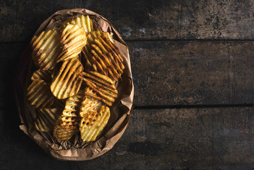 Homemade and baked potatoes chips on the wooden background with blank space