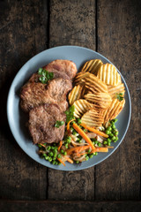 Pork steak with potatoes chips and vegetables served on the table