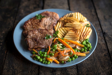 Pork steak,potatoes chips and vegetables served in the table,selective focus