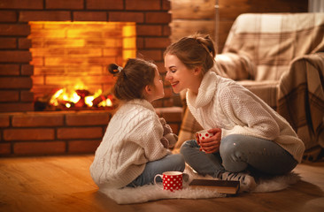 family mother and child drinking tea and laughing on winter evening by fireplace.