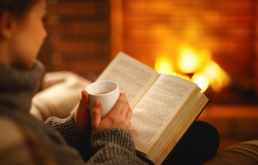 book and cup of coffee in hands of girl on  winter evening near fireplace