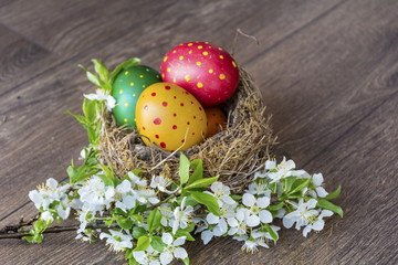 Easter Eggs with in real nest with cherry blossoms on a  wooden background. Easter decoration
