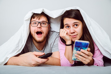 man interesed with movie womn bored searfing phone