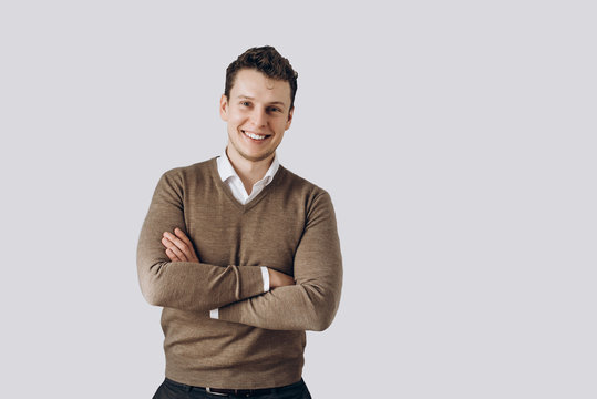 Portrait of a handsome cheerful guy who stands near a white wall on which there is space for text