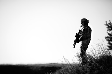 military soldier with weapons at sunset. shot, holding gun, colorful sky. military concept.