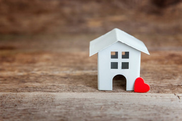 Miniature white toy house with red hearts on a wooden table. Mortgage property insurance dream home concept