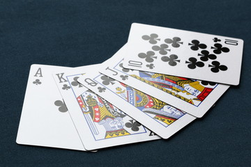 Royal flush (poker hand) of clubs on a dark background