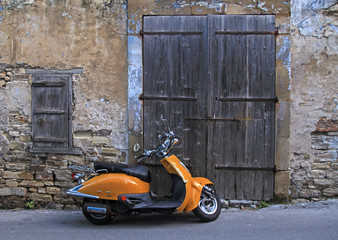 street in old village with wood door and old scooter