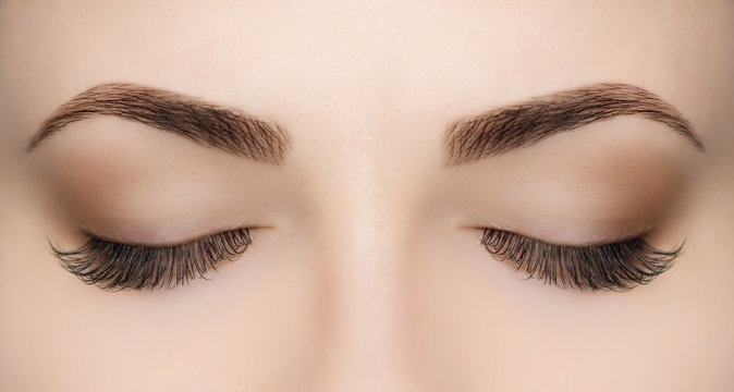 Beautiful Woman with long lashes in a beauty salon. Eyelash extension procedure.