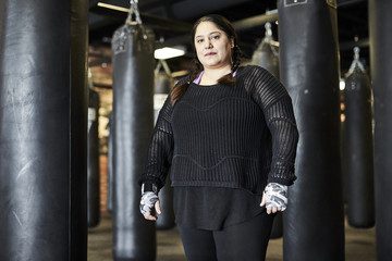 A three quarter portrait of a female boxer in a boxing gym.