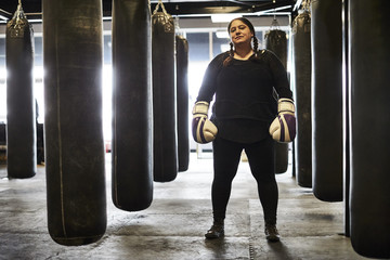 A full body portrait of a female boxer amongst the heavy punching bags.