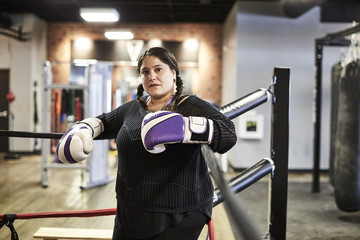 A female boxer poses for a portrait in the corner of the ring.