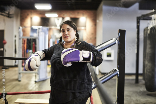 A female boxer poses for a portrait in the corner of the ring