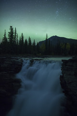 Waterfall under Aurora Borealis at night in Jasper National Park, Alberta, Canada