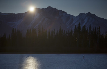 Scenery with mountain range, forest and lake or river at night, Banff National Park, Alberta, Canada