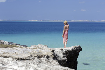 Woman standing alone on edge of coastal cliff and admiring Indian Ocean, Mozambique