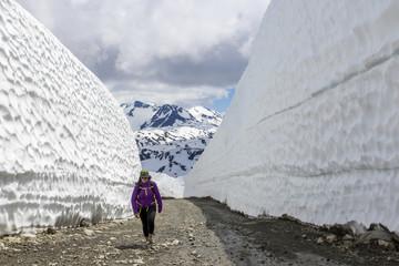 Woman hiking on road between snow walls, Whistler Blackcomb, Whistler, British Columbia, Canada