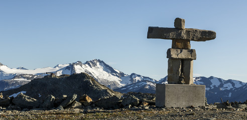 Inuksuk cairn against mountain range and clear sky, Whistler, British Columbia, Canada