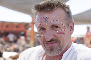 Portrait of male festival goer wearing face paint, San Bernardino County, California, USA