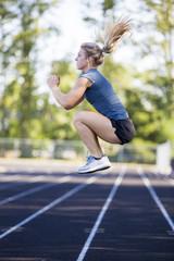 Young woman exercising on track, Eugene, Oregon, USA