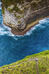 Aerial view of couple hiking along Nusa Penida coastal cliff, Bali, Indonesia