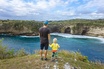 Father and son standing on edge of coastal cliff and admiring ocean, Bali, Indonesia