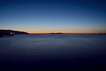 blue hour in mediterranean sea from the vlora beach in albania with sazan and karaburun island
