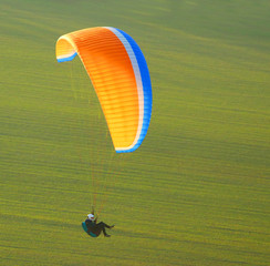 Paraglider flying over a mountain meadows. Paragliding sport.