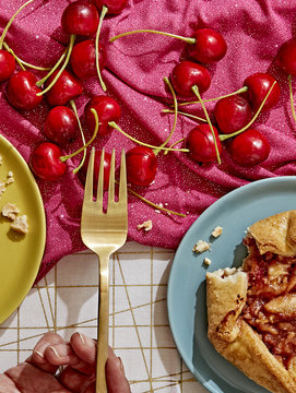 Close-up of woman's hand eating cherries and pastry