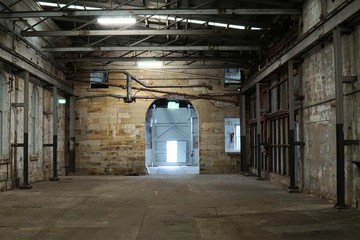 Autocollant pour porte Les vieux bâtiments abandonnés Inside of old abandon factory. A structure interior of empty industry warehouse. An abandon old factory with no equipment and machine. Image of rustic factory room structure made from iron and steel.