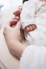赤ちゃんを抱く母親の手