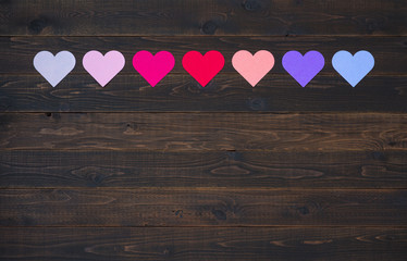 Colorful Valentine's Day Hearts in Pinks, Red, Purple, Lavender Tones laying on a Dark Rustic Wood Board Background with room or space for copy, text, your words or design.  A Horizontal flay lay