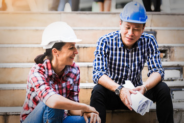 Engineers man and woman working on plan building construction in city