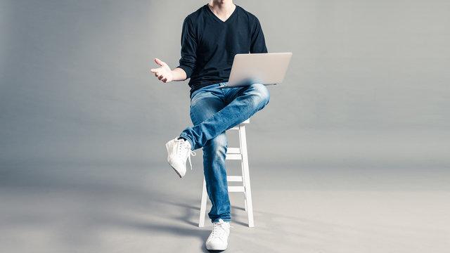 パソコンを持って椅子に座っているカジュアルな服装の男性
