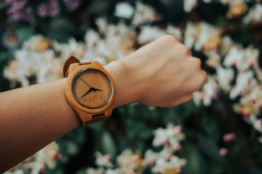 hand business woman wearing wooden watch with copy space and beautiful colorful flowers background. image for valentine, nature, ornamental, accessory, blossom, spring, decorate, garden concept